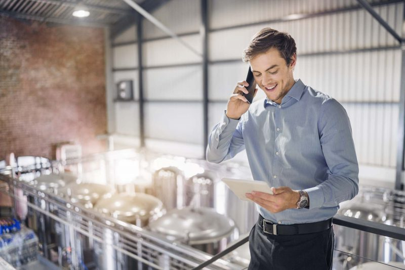 Happy male worker using digital tablet while talking on smart phone. Confident professional is in formals. He is working at brightly lit beer industry.