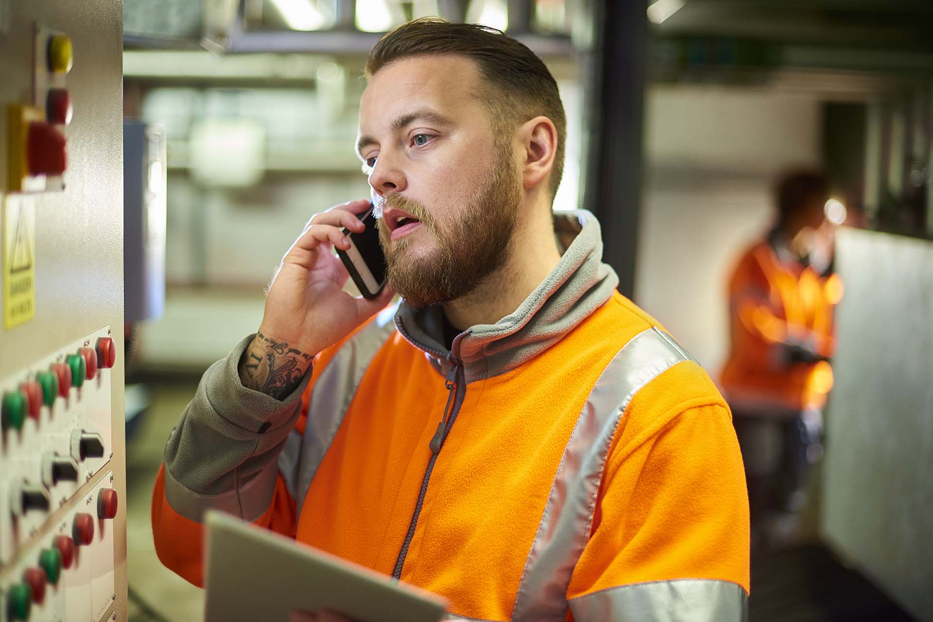 An industrial service engineer conducts a safety check of a control panel in a boiler room. He is wearing hi vis and is on the phone to technical support double checking his decision on how to fix a technical problem.