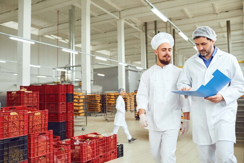 The technologist and baker speak in a bread factory. Factory workers in the workplace.
